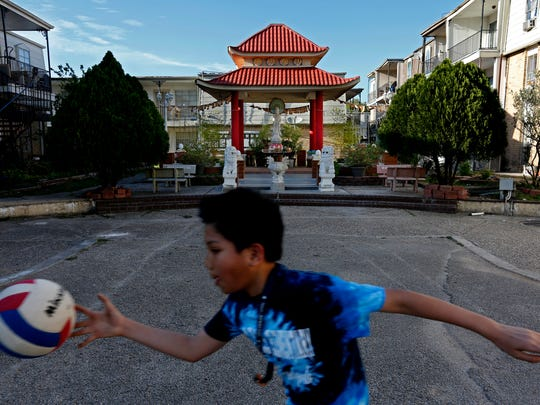 Children play in the courtyard of the Thai Xuan Village in Houston. A Catholic priest and Vietnamese refugee purchased the complex in the 1980s, creating a Vietnamese village where about 1,000 residents live.
