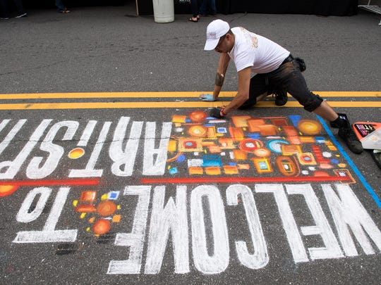 "Matt Gutierrez creates a sidewalk chalk mural that says ""Welcome to Artisphere"" during the first day of the event in downtown Greenville on Friday, May 12, 2017."
