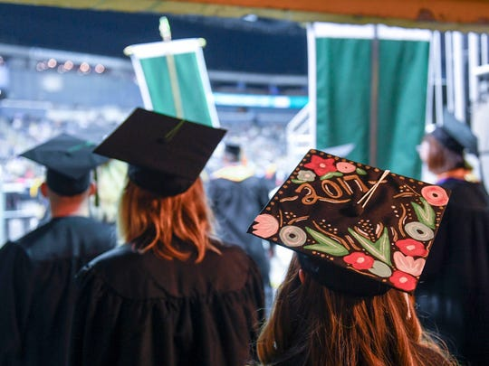 Ivy Tech graduates walk out into the Ford Center for the school's commencement ceremony Friday, May 12, 2017.