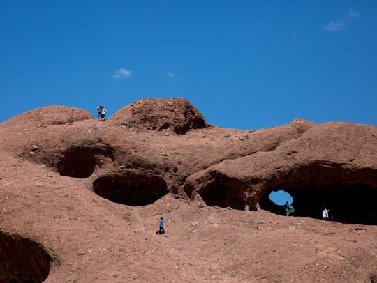 People hike Hole in the Rock at Papago Park in Phoenix
