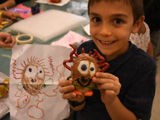 A student named Rylan shows his drawing, and the 3-D version. Kindergarden students at Pelican Marsh Elementary School had their drawings of monsters rendered in three-dimensional clay by ceramics students at Barron Collier High School, in a cooperative learning initiative between the two schools.