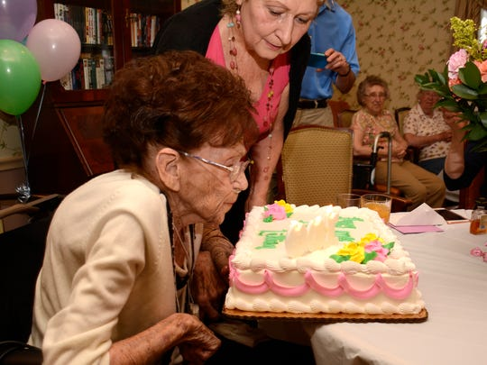 Lillian Olsh blows out the candles on her 100th birthday with niece Susan Wilson looking on.