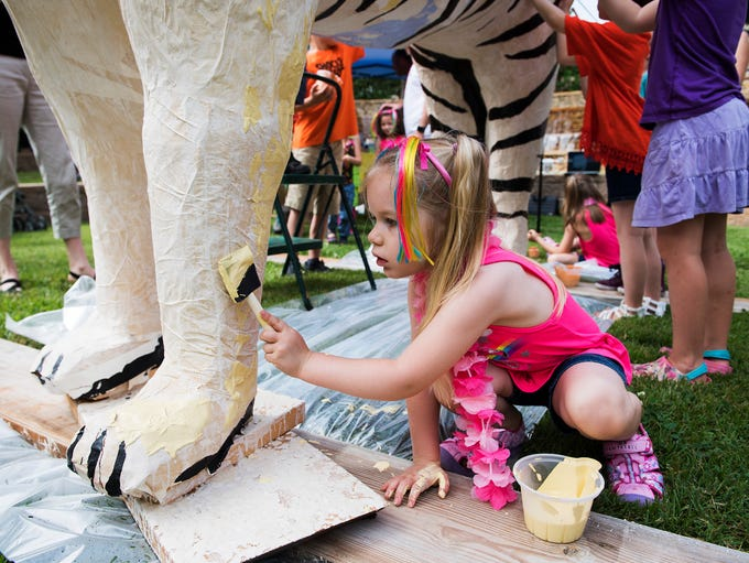Evelina Boska, 4, pains a paper mache tiger during