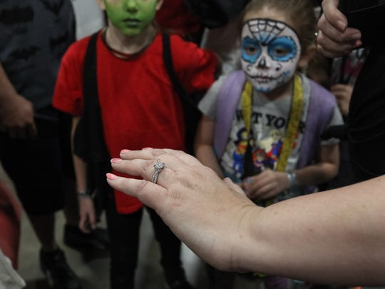 Mari Kaskorkis displays her new engagement ring to friends and family after accepting a surprise proposal from her boyfriend during the Motor City Comic Con at the Suburban Collection Showplace in Novi on Saturday, May 20, 2017.