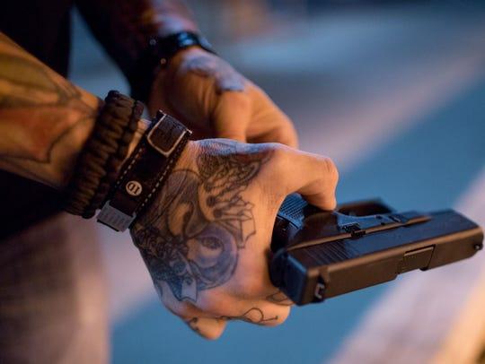 Thomas Yoxall shows the firearm he keeps on his hip.