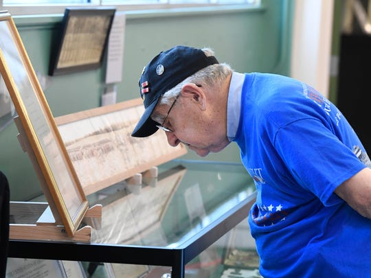 World War II veteran Bob Collier looks through a display case during the opening of the Evansville Wartime Museum on May 27, 2017. Collier served in the Army Air Corp as a radio operator in the Aleutian Islands.