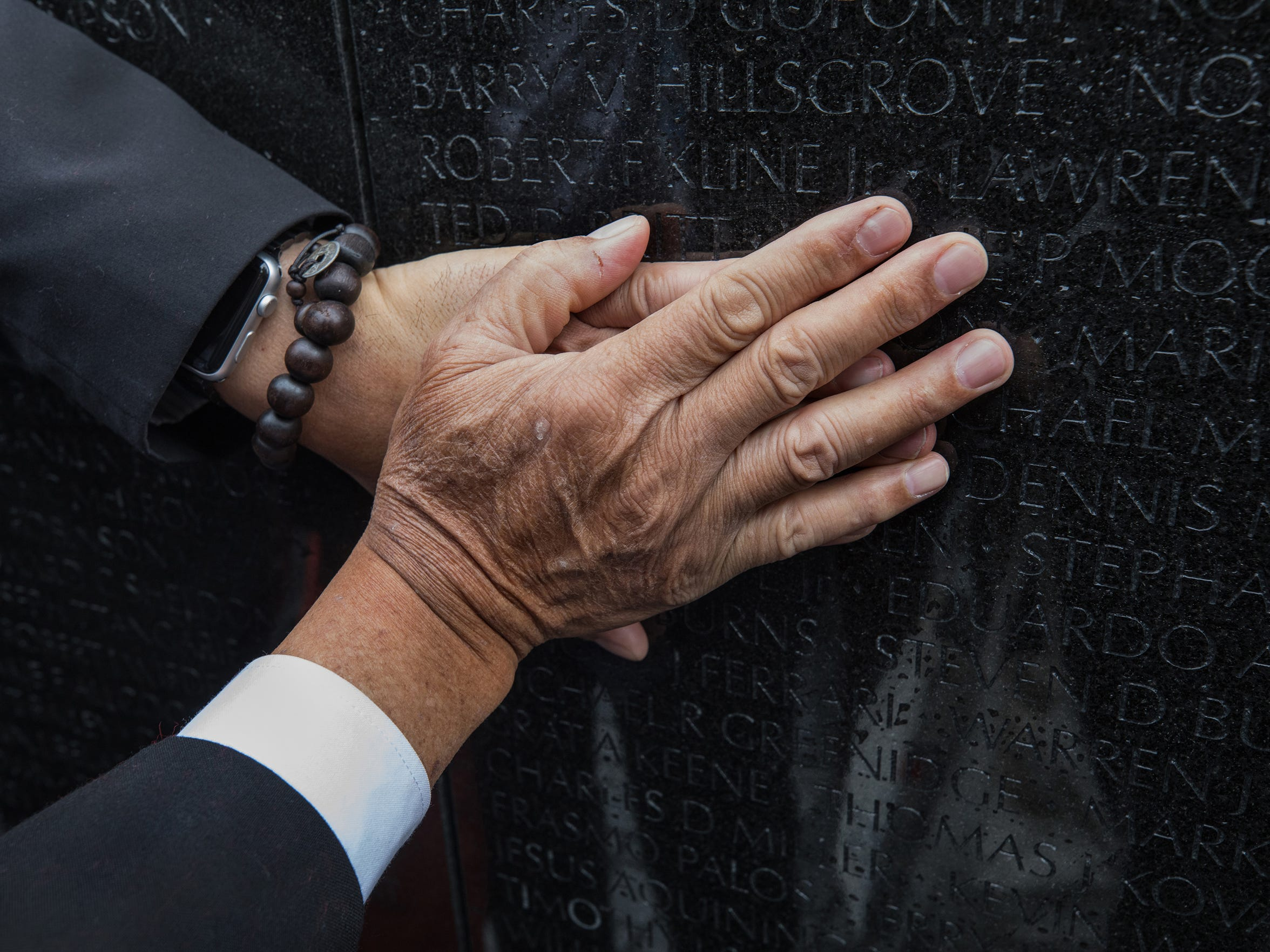 Vu Ngoc Xiem places his hand over Ron Reyes' hand as Ron touches his father's name etched into the Vietnam Veterans Memorial on Thursday. Their fathers were on opposing sides during the Vietnam War; the two sons are part of the 2 Sides Project.
