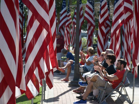 Spectators sit in the Aisle of Flags, honoring 100 deceased area servicepeople. The City of Bonita Springs commemorated Memorial Day with a ceremony Monday morning at Riverside Park.