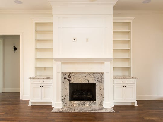 The living area has built-in shelves and a granite fireplace