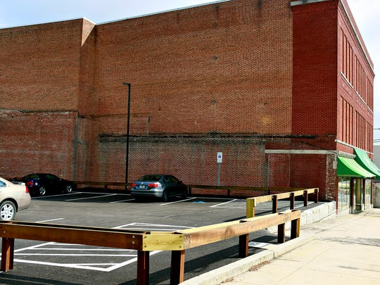 The Zarfos Furniture building is shown next to a parking lot, built by the borough, which is adjacent to their property in Red Lion, Wednesday, May 31, 2017. Zarfos building owners Scott Thompson and Sandra Graham recently won a lawsuit against the borough, for essentially using their building as a retaining wall for the lot, with the court ruling the act as trespassing. Dawn J. Sagert photo