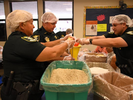 Lee County Sheriffs deputies including Charlene Ellison, left, fill bags with eight portions of apple cinnamon oatmeal.