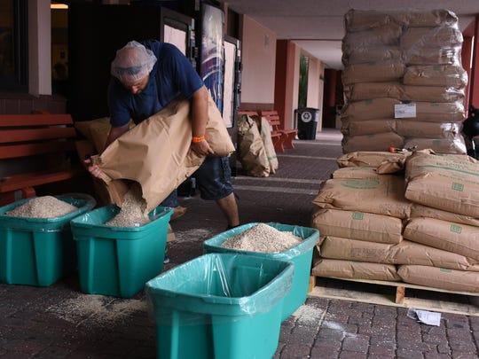 Nicholas MacArthur fills tubs from 50-pound sacks of oatmeal.
