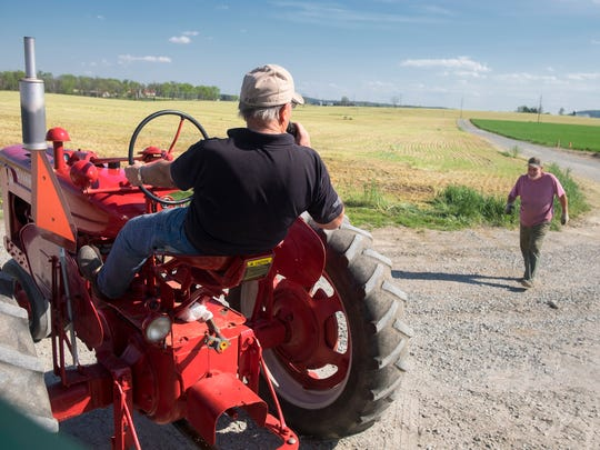 Luke Brubaker, 76, sits on his tractor as his son Mike  greets him on the family's dairy farm on April 18, 2017 in Mount Joy, Pa. (Ed Hille/Philadelphia Inquirer/TNS)