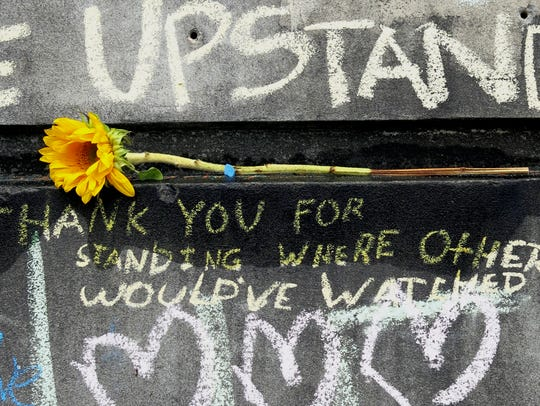 A flower and message are shown at a memorial in Portland,