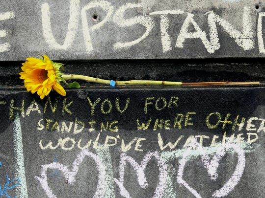 A flower and message are shown at a memorial in Portland, Ore., Tuesday, May 30, 2017, for the victims who were fatally stabbed while trying to stop a man from shouting anti-Muslim insults at two young women on a Portland light-rail train. The suspect in last week's attack, Jeremy Joseph Christian, made a first court appearance in Portland on charges of aggravated murder and attempted murder on Tuesday. (AP Photo/Gillian Flaccus)