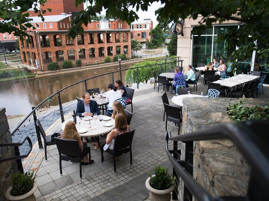 Guests enjoy dinner on the patio of The Lazy Goat in downtown Greenville on Thursday, June 8, 2017.