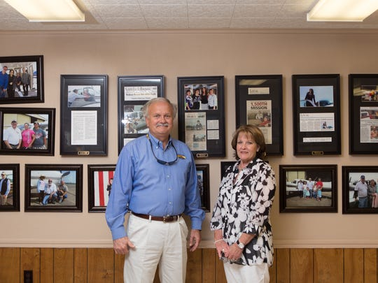 Phillip and Sharon in front of framed photos and articles in their hangar