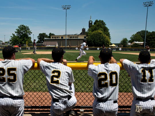 Jasper's Austin Simmers ran to first base as teammates Mason Thewes, left, Tanner Egbert, Seth Mendel and Cameron Heeke watched from the dugout during Saturday's Class 3A baseball semistate game at Ruxer Field in Jasper. Jasper defeated Northview 3-2 in 10 innings.