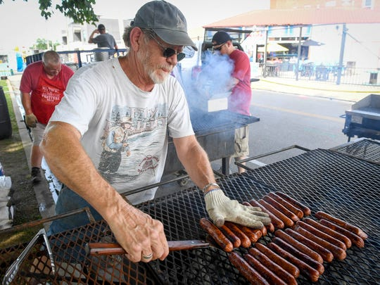 "Luther Burton takes smoked sausages off the grill as volunteers prepare for the hungry crowds attending the W.C. Handy Blues and Barbecue Festival ""Zydeco Night"" Thursday, June 15, 2017."