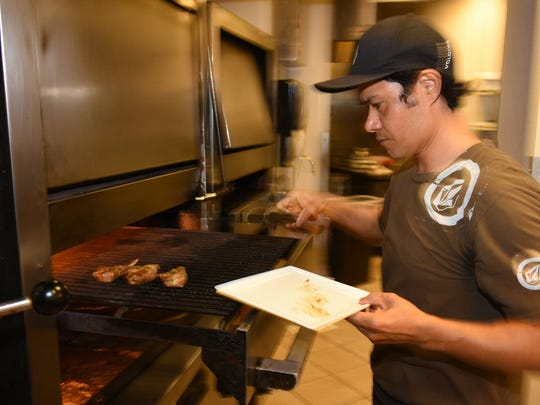 """Chop 239 chef Javier Sanchez sears lamb chops, an item that will be on Sunday's menu. Wine and food pairings will tantalize the palate at """"The Glory of the Grape,"""" the Chamber of Commerce event hosted this year at Chop 239 on Sunday evening."""