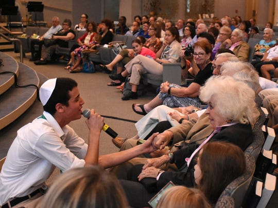 Jonathan Kantarowic, left, does some audience participation at Temple Shalom on Tuesday. The Israel Scouts Friendship Caravan, with 10 teenage performers and two leaders, gave five performances in two days at Naples venues during their barnstorming tour of the U.S.