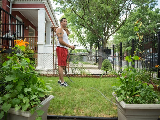 Cesar Serrano waters his lawn just south of the Bloomingdale