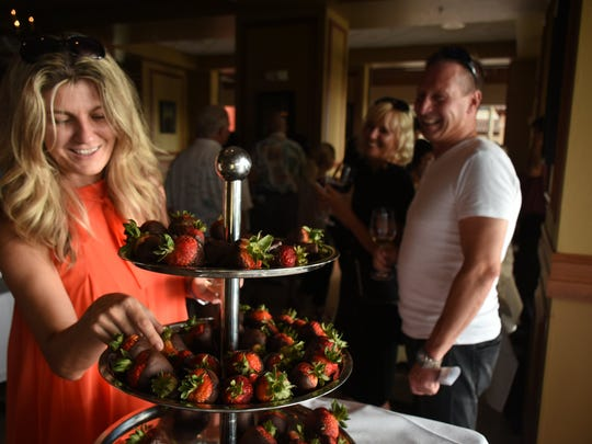 """Strawberry blonde - Mila Bridger picks a dessert to nibble. """"Glory of the Grape,"""" the Chamber of Commerce fundraiser, was held Sunday evening for the first time at a new venue, Chop 239 in the Esplanade."""