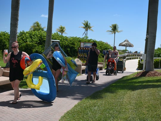 Beachgoers return from the shore with their toys. MICA's Residents' Park will be headquarters for Uncle Sam's Sand Jam on the Fourth of July, with the beach packed for spectators during the fireworks display.