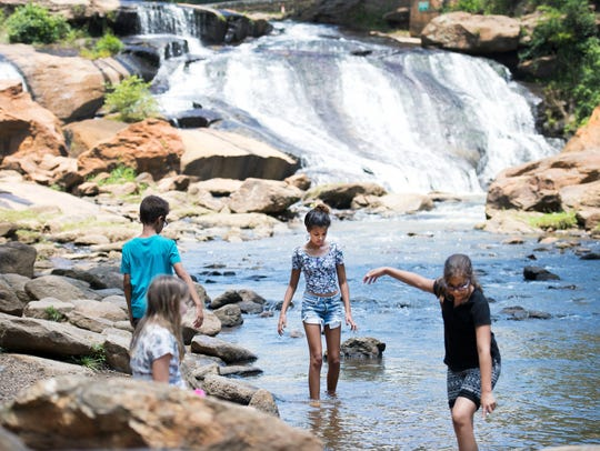 Children wade in the Reedy River in Falls Park on Thursday,