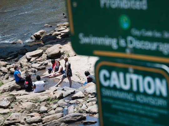 A group of people sit with their legs in the Reedy River as a sign warns swimmers that they could get sick from the water on Thursday, June 15, 2017.