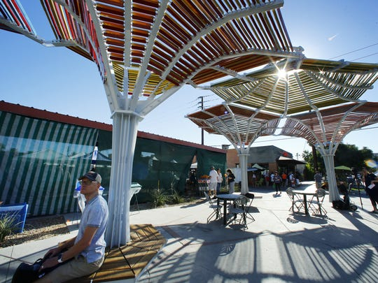 People enjoy Bloomcanopy, a major new downtown shade and public art project Saturday, July 1, 2017 in Phoenix,  Ariz.  The piece was commissioned by the City of Phoenix Office of Arts and Culture to design shade enhancements for Pierce Street, in front of the Phoenix Public Market.