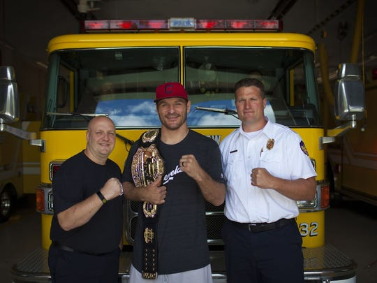 Stipe Miocic, center, shows off his championship belt
