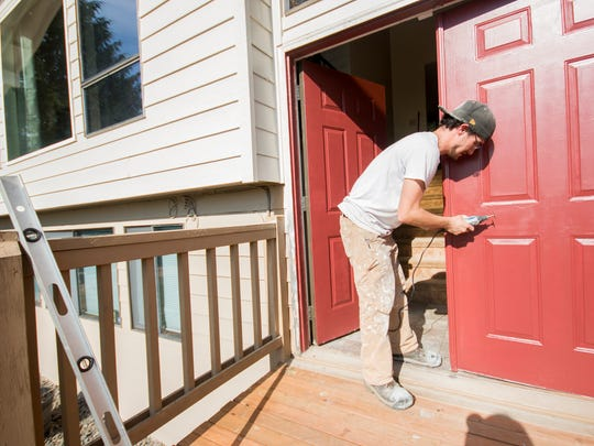 Volunteer AJ Handley finishes the final touches on the newly restored door to the front of the Randle family house in Poulsbo.