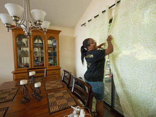 A volunteer finishes hanging up the curtains in the kitchen of the house.