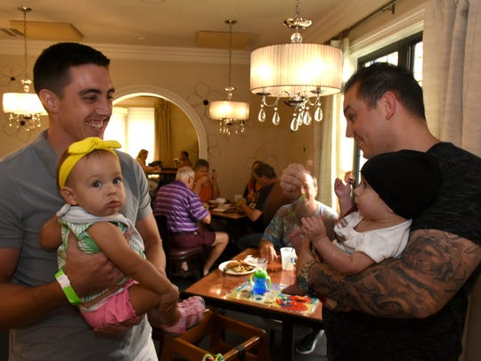 A fix-up? Nick and Cash Macchiarolo, right, talk with Levi Conroy and his daughter Lilyana. La Tavola restaurant hosted a fundraiser on Sunday for baby Cash, son of Marco Island firefighter Nick Macchiarolo and his wife Gabriella, to help with his considerable medical expenses.