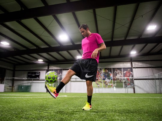 Anthony Esquivel juggles a soccer ball on the turf