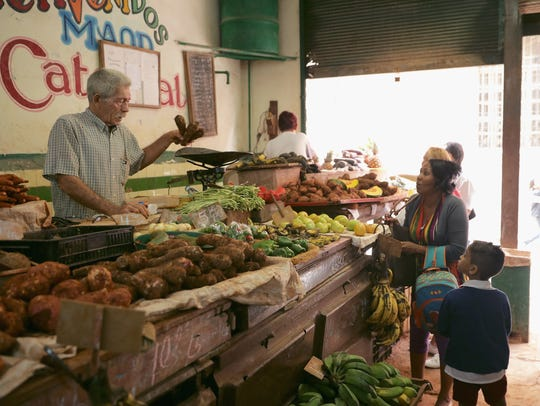 Cubans shop for fruits and vegetables in the historic