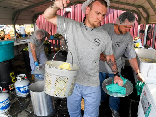 In this file photo from July 2017, Henderson County Detention Center inmates Jeffrey Jennings (left) and Brian Hawks blanch sliced squash before packing and freezing the produce in a outdoor kitchen at the facility.