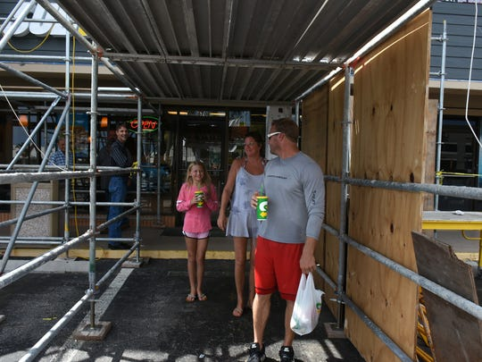 Subway sandwich seekers Steve, Vicki and Rylee Howard navigate the forest of scaffolding. Shops and restaurants in the Island Plaza remain open during construction, but not everyone realizes it, with scaffolds and construction materials hiding the storefronts.