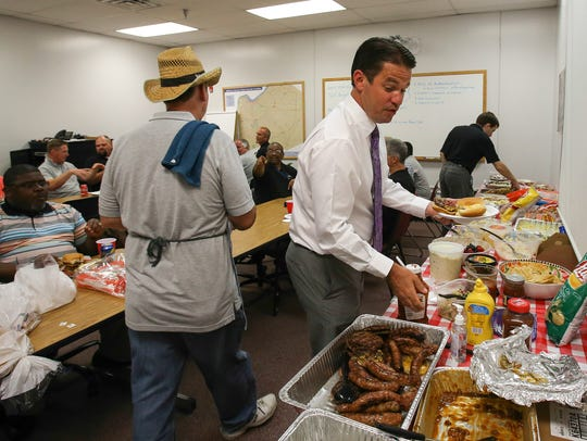 Marty Pollio fills up his plate at a barbecue put on