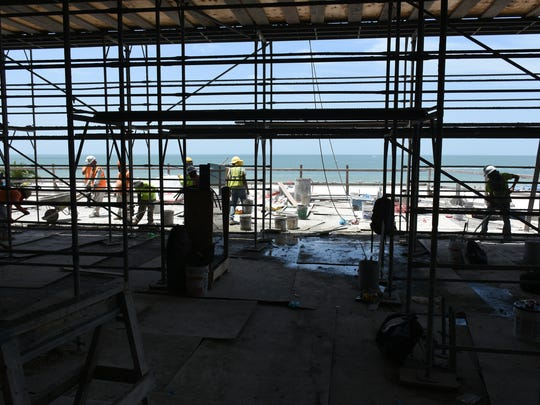 """Concrete finishers work in front of the """"million dollar view."""" Work continues at Marco's JW Marriott hotel, with final completion pushed back by enhancements to the new wing."""