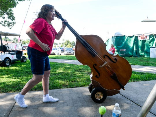Sandy Rogers with the Bluegrass Fever band wheels her bass backstage at the 32nd annual Bluegrass in the Park/Folklife Festival in Henderson's Audubon Mill Park Saturday, August 12, 2017.