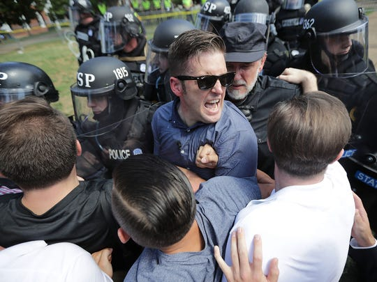 "White nationalist Richard Spencer, center,  and his supporters clash with Virginia State Police in Lee Park after the ""United the Right"" rally was declared an unlawful gathering Aug. 12, 2017 in Charlottesville, Virginia. Hundreds of white nationalists, neo-Nazis and members of the ""alt-right"" clashed with anti-facist protesters and police as they attempted to hold a rally in Lee Park, where a statue of Confederate General Robert E. Lee is slated to be removed."