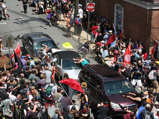 A gray Dodge plowed into pedestrians and vehicles on the mall in Charlottesville after Saturday's white supremacist rally. The Mustang driver hit the knot of cars and people at high speed, then backed up and fled the scene. Serious, maybe life-threatening injuries to several people.