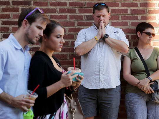 People gather and pray at an informal memorial where 32-year-old Heather Heyer was killed when a car plowed into a crowd of people protesting against the white supremacist Unite the Right rally on Aug. 13, 2017 in Charlottesville, Va.