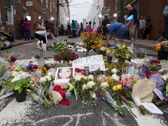 The memorial on 4th street is built up with more flowers while two spectators drop their on bouquets into the formation. Following protests that turned violent on Saturday and a day of memorial and mourning on Sunday, the town of Charlottesville, Virginia, continues to recover from the social rift on Monday, with both continued memorials, the denial of bail for James Alex Fields Jr., and a move towards regular city activities.