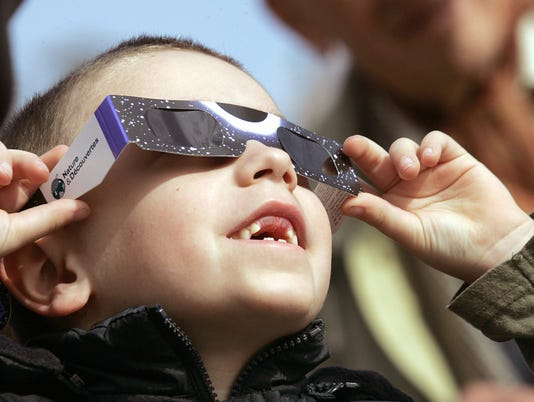 A French child watches a solar eclipse,