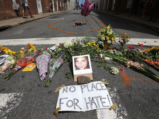 Flowers surround a photo of 32-year-old Heather Heyer, who was killed when a car plowed into a crowd of people protesting against the white supremacist Unite the Right rally on Aug. 13, 2017, in Charlottesville, Virginia.