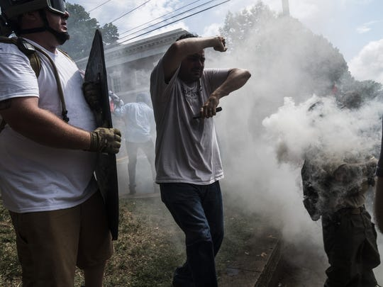 Alt-right rally members get hit by smoke grenade thrown out by counter protesters on Saturday Aug. 12, 2017 in Lee Park in Charlottesville, Va. (Go Nakamura/Zuma Press/TNS)