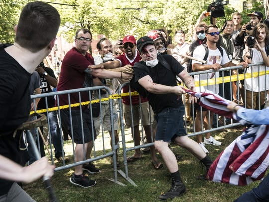 A counter protester who got hit with a stick by an alt-right member is covered with blood on his face on Saturday Aug. 12, 2017 in Lee Park in Charlottesville, Va. (Go Nakamura/Zuma Press/TNS)